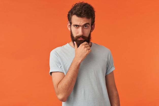 Retrato de jovem barbudo bonito olhando para você de pé contra a parede vermelha braço toque barba emoção cético duvidoso cínico