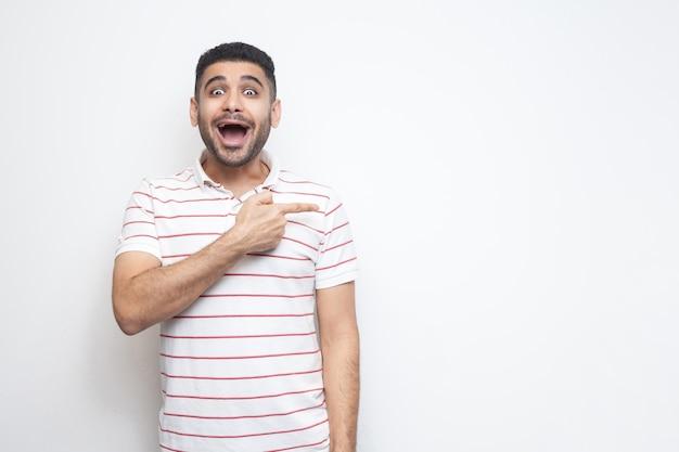 Retrato de jovem barbudo bonito surpreso em pé de camiseta listrada, olhando para a câmera com rosto espantado e apontando para o espaço vazio da cópia da parede. tiro de estúdio interno, isolado no fundo branco