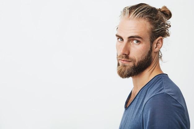 Retrato de jovem barbudo com penteado na moda e barba