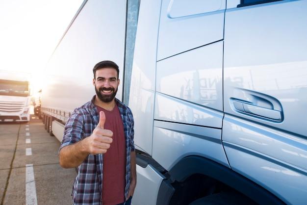 Retrato de jovem barbudo com polegares para cima em pé perto de seu caminhão.