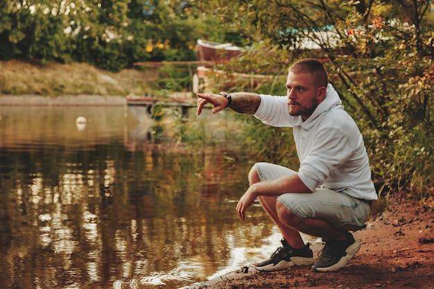 Retrato de jovem barbudo com tatuagens na jaqueta branca na zona rural ou no parque. homem com roupas casuais passa a noite na natureza. conceito de estilo, caminhar ao ar livre e união com a natureza