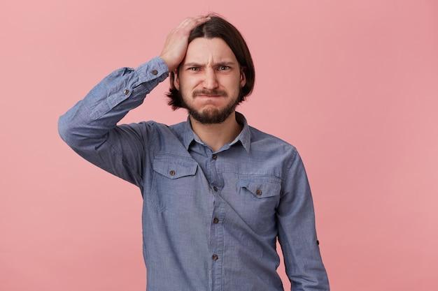 Retrato de jovem barbudo em camisa jeans, segurar sua cabeça, soprando as bochechas e mordidas os lábios, esqueceu algo importante, cometeu um erro. isolado sobre o fundo oink.