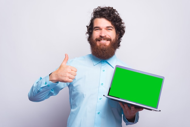 Retrato de jovem barbudo em casual mostrando o polegar para cima gesto e segurando o laptop com tela verde