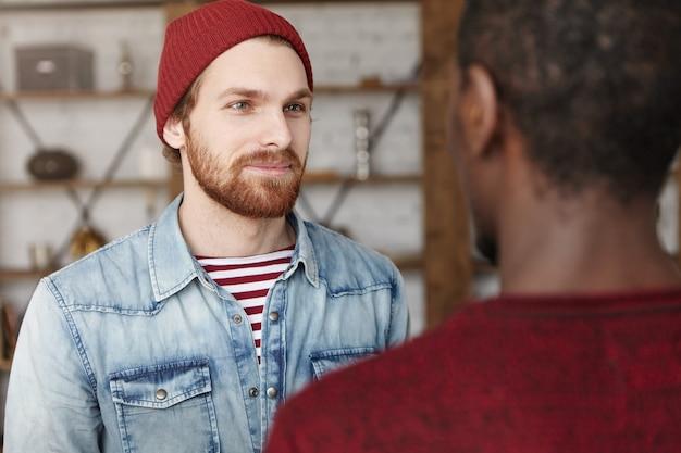 Retrato de jovem barbudo hippie alegre, usando chapéu da moda e jaqueta jeans