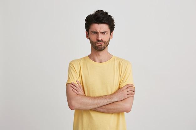 Retrato de jovem barbudo sério e estrito vestindo camiseta amarela, fica com raiva e mantém os braços cruzados isolados no branco