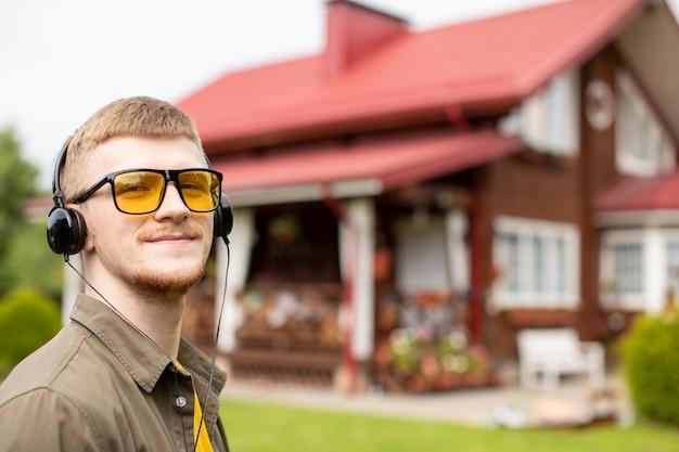 Retrato de jovem barbudo sorridente de óculos amarelos vestido casualmente, ouvindo música online através de fones de ouvido modernos. aconchegante casa de campo na rua turva.