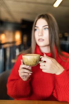 Retrato de jovem bebendo café na mesa com o notebook no café