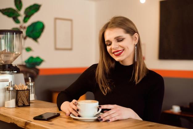 Retrato de jovem bebendo café no café.