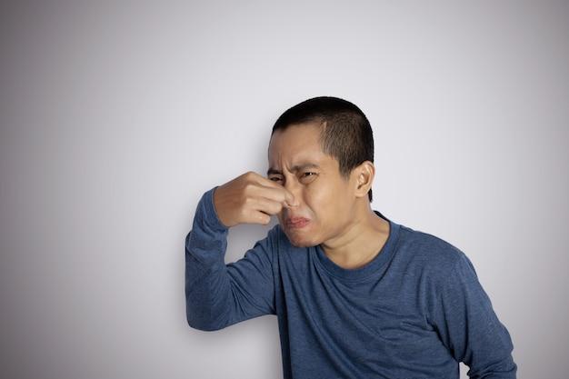 Retrato de jovem beliscando o nariz no rosto devido ao mau cheiro isolado em fundo cinza