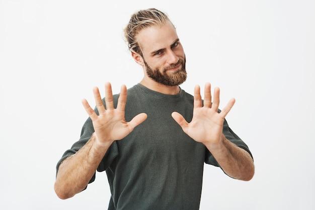 Retrato de jovem bonitão com corte de cabelo na moda e barba gesticulando com as duas mãos