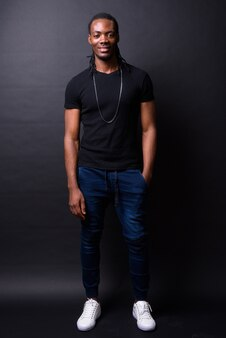 Retrato de jovem bonito africano com dreadlocks no preto
