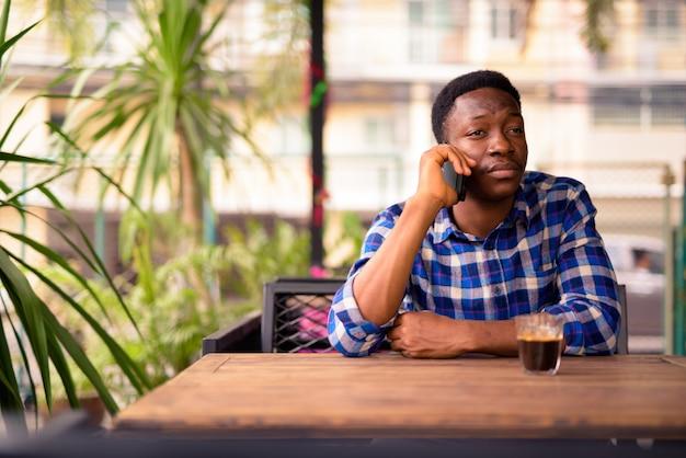 Retrato de jovem bonito africano relaxando na cafeteria