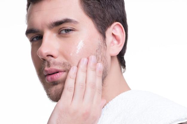 Retrato de jovem bonito, aplicando a loção creme no rosto - isolado no branco.