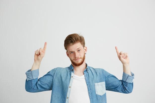 Retrato de jovem bonito, apontando o dedo para cima.