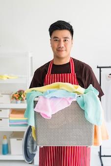Retrato de jovem bonito asiático carrega o cesto de roupa suja com toalhas coloridas para lavar na máquina de lavar. trabalho doméstico em casa no fim de semana.