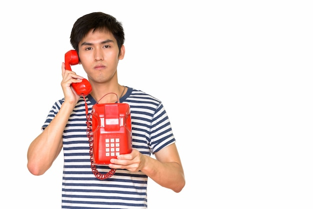 Retrato de jovem bonito asiático falando ao telefone, isolado contra uma parede branca