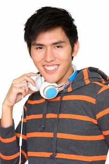 Retrato de jovem bonito asiático sorrindo com fones de ouvido isolados contra uma parede branca