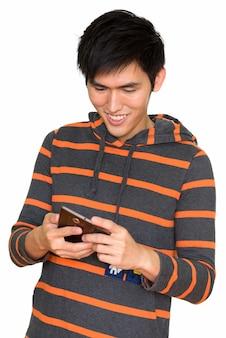 Retrato de jovem bonito asiático sorrindo e usando telefone celular isolado contra uma parede branca