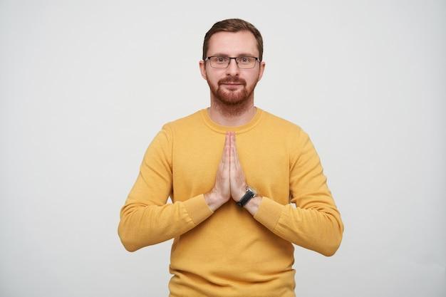 Retrato de jovem bonito barbudo com corte de cabelo curto, rosto calmo e palmas dobradas em gesto de namastê, posando com um pulôver mostarda