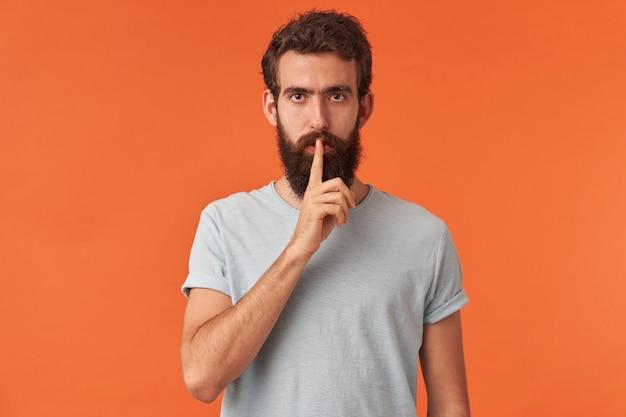 Retrato de jovem bonito barbudo com olhos castanhos em t-shirt branca mostra dedo na boca, olhando para você emoção, silêncio atento e confiante