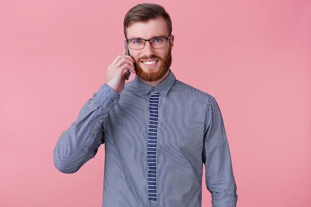 Retrato de jovem bonito barbudo de óculos e uma camisa listrada, falando ao telefone e sorrindo amplamente isolado sobre fundo rosa.