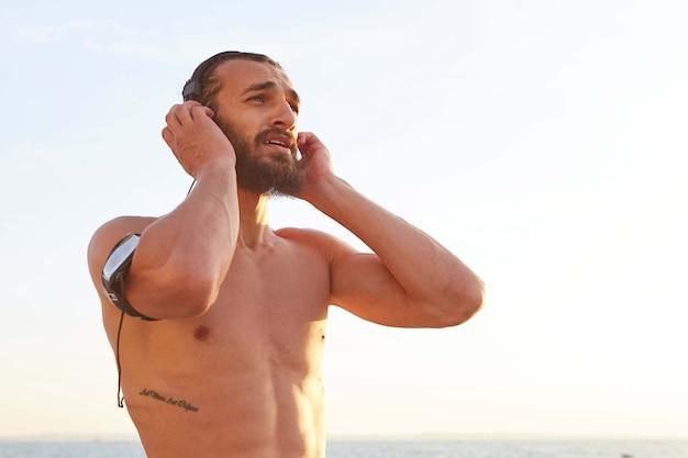 Retrato de jovem bonito barbudo jovem descansar depois de correr à beira-mar, ouvindo a música favorita em fones de ouvido.