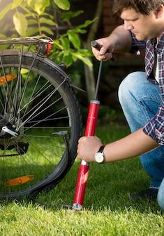 Retrato de jovem bonito bombeando pneus de bicicleta no parque