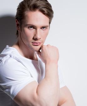 Retrato de jovem bonito com a mão perto do rosto em poses de camiseta branca na parede com sombras de contraste.