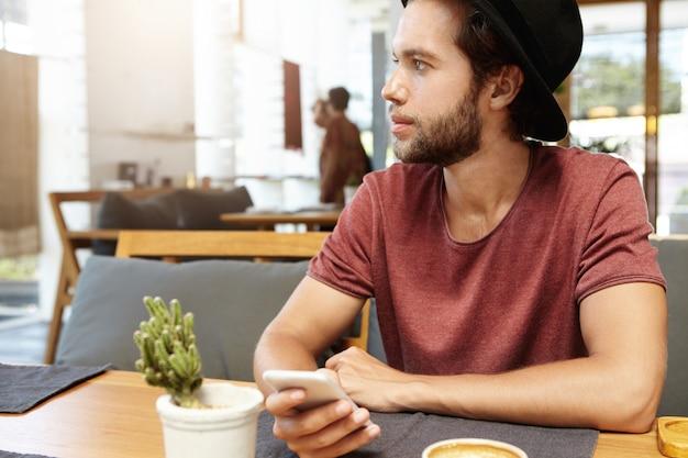 Retrato de jovem bonito com barba por fazer, sentado à mesa de madeira, segurando um telefone inteligente genérico