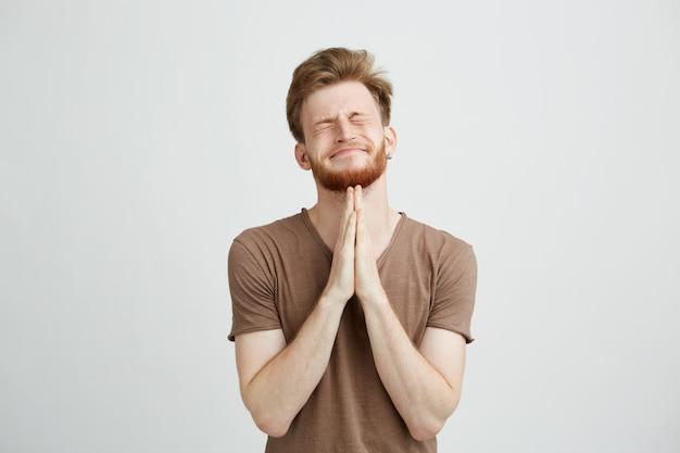 Retrato de jovem bonito com barba rezando na esperança.