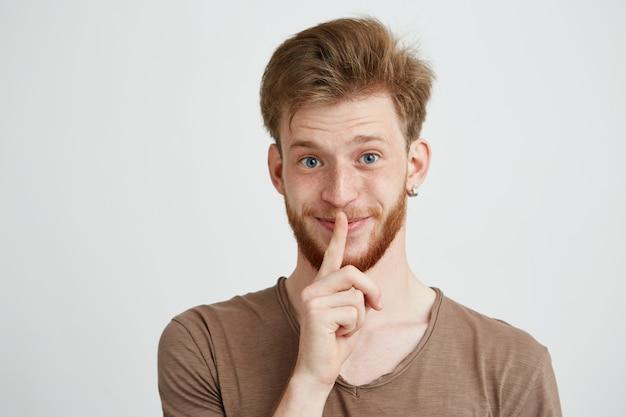 Retrato de jovem bonito com barba sorrindo mostrando para manter o silêncio.