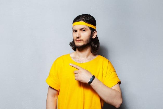Retrato de jovem bonito com cabelo comprido em uma camisa amarela, apontando o dedo para longe