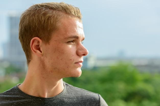 Retrato de jovem bonito com cabelo loiro, contra a vista da cidade