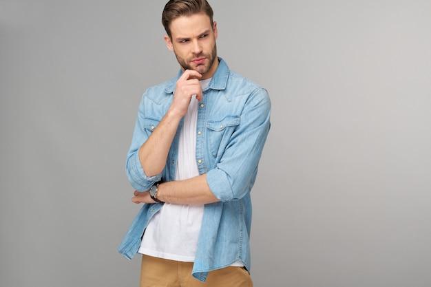 Retrato de jovem bonito com camisa jeans sobre parede de luz