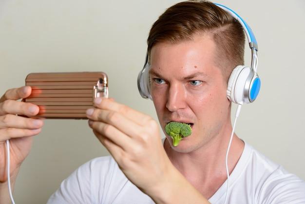 Retrato de jovem bonito com fones de ouvido, comendo brócolis e tomando selfie