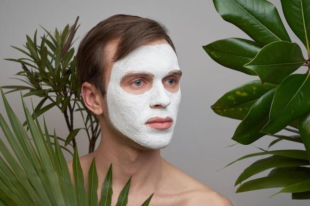 Retrato de jovem bonito com máscara cosmética branca no rosto contra plantas verdes.