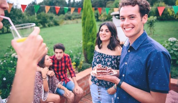 Retrato de jovem bonito com um pedaço de bolo nu nas mãos se divertindo em um churrasco de verão ao ar livre com seus amigos