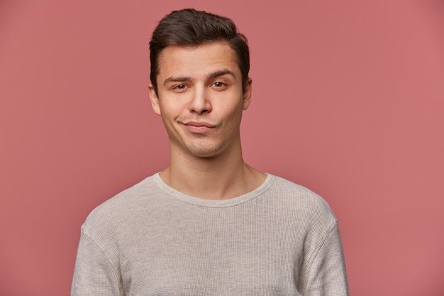 Retrato de jovem bonito com uma sobrancelha levantada em desaprovação, usa uma camiseta em branco, olha para a câmera com um sorriso e dúvidas, fica sobre um fundo rosa.