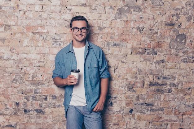 Retrato de jovem bonito com uma xícara de café no espaço da parede de tijolos