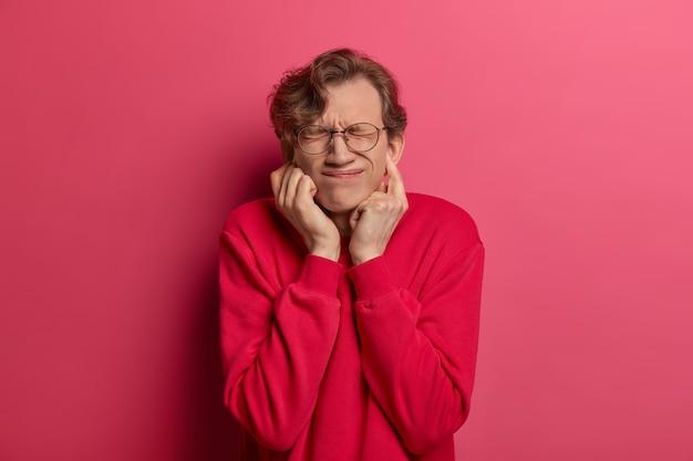 Retrato de jovem bonito do sexo masculino tapa os ouvidos, mantém os olhos fechados de desagrado, sofre com um som nojento, ignora problemas, sorri afetadamente, vestido casualmente, isolado na parede rosa