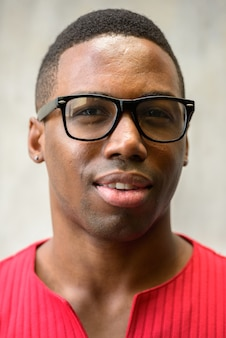 Retrato de jovem bonito e musculoso africano com óculos contra uma parede de concreto ao ar livre