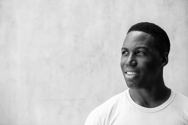 Retrato de jovem bonito e musculoso africano contra uma parede de concreto ao ar livre em preto e branco