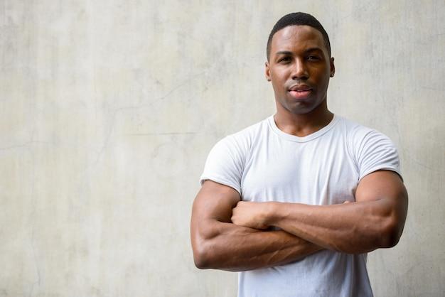 Retrato de jovem bonito e musculoso africano contra uma parede de concreto ao ar livre