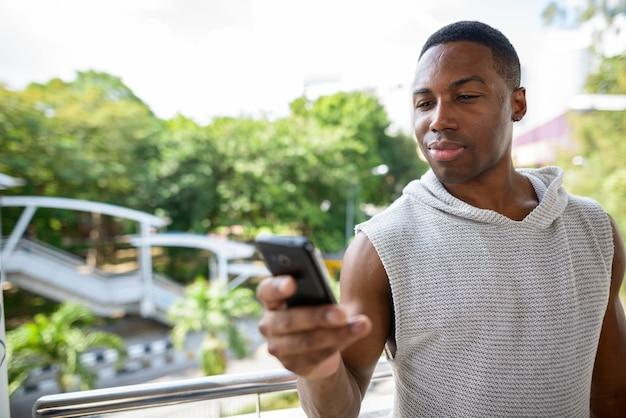 Retrato de jovem bonito e musculoso africano pronto para a academia contra a vista das ruas da cidade