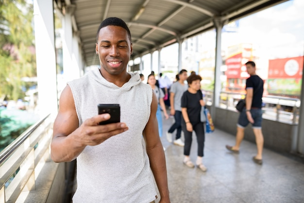 Retrato de jovem bonito e musculoso africano pronto para a academia na passarela da cidade