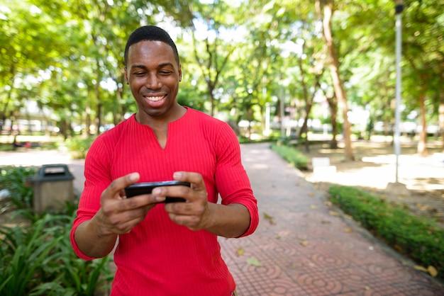 Retrato de jovem bonito e musculoso africano relaxando no parque ao ar livre