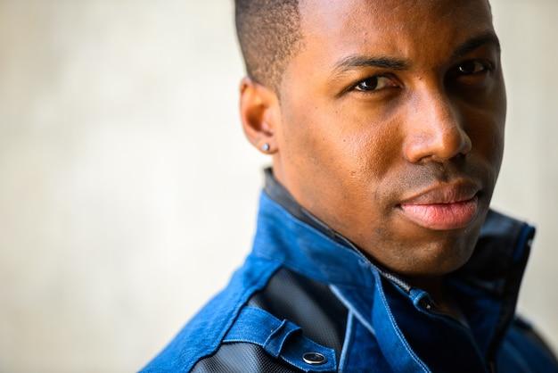Retrato de jovem bonito e musculoso africano vestindo jaqueta azul contra uma parede de concreto ao ar livre