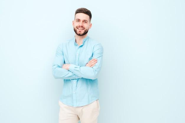 Retrato de jovem bonito e sorridente, vestindo calça e camisa casual
