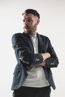 Retrato de jovem bonito elegante de pé contra branco. homem vestindo jaqueta