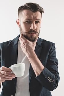 Retrato de jovem bonito elegante em pé no estúdio. homem vestindo jaqueta segurando uma xícara de café